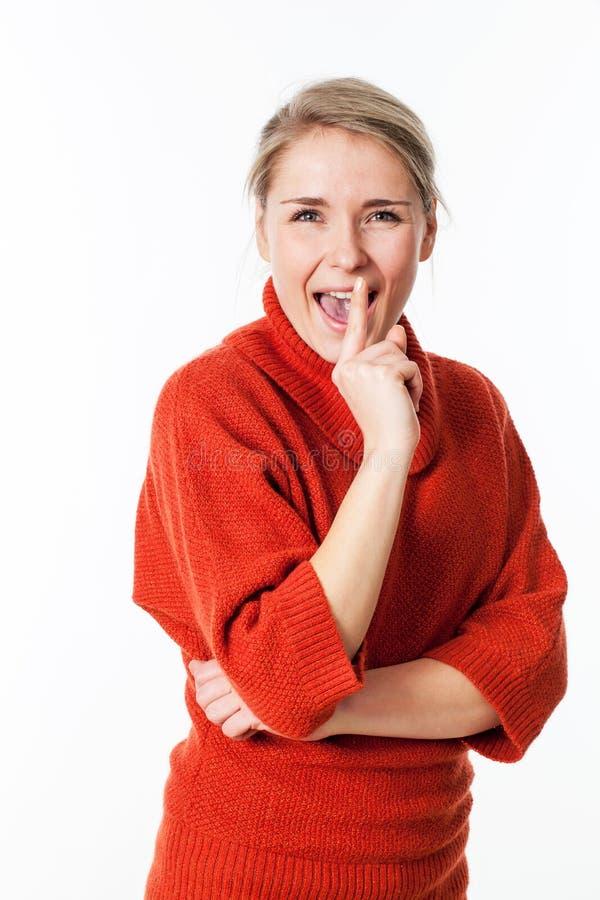 Vrouw die met index op lippen voor pretgeheimzinnigheid lachen royalty-vrije stock foto's