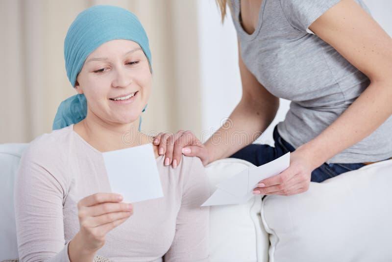 Vrouw die met kanker foto bekijken stock afbeeldingen