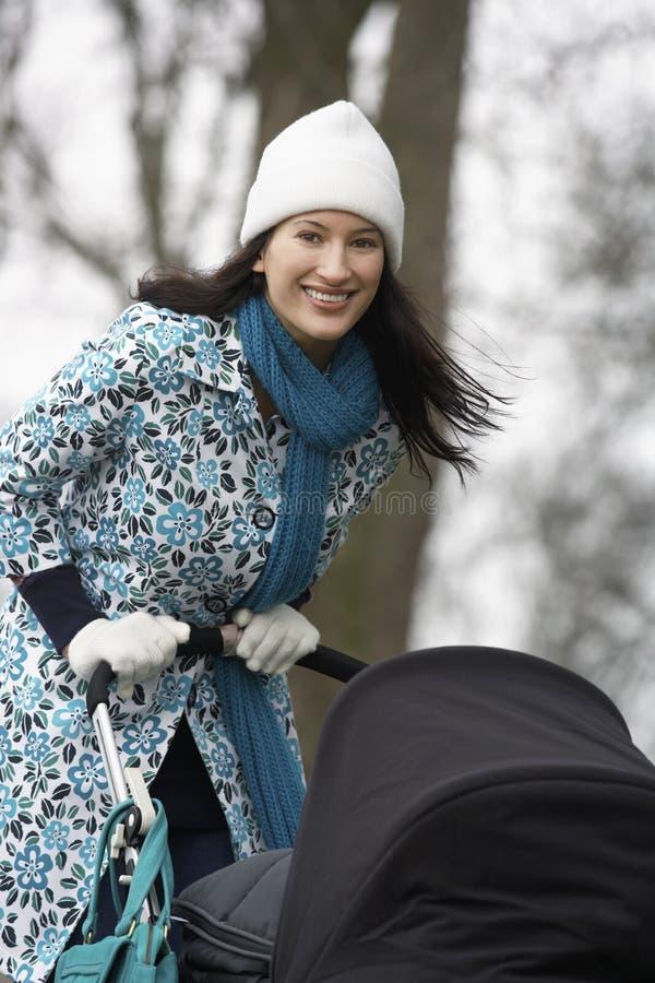 Vrouw die met Kinderwagen in Park lopen royalty-vrije stock afbeeldingen