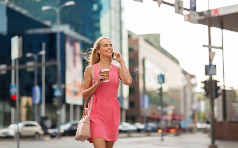 Vrouw die met koffie smartphone in stad uitnodigen royalty-vrije stock afbeelding