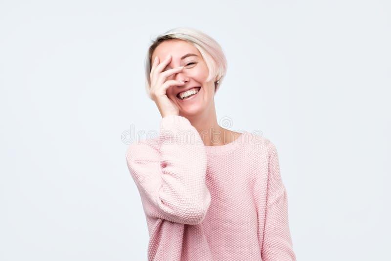 Vrouw die met kort geverft haar in roze sweater sluitend haar gezicht met hand lachen stock foto