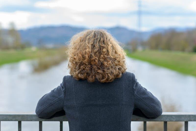Vrouw die met krullend haar de rivier bekijken stock afbeelding