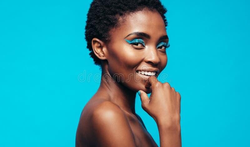 Vrouw die met make-up tegen blauwe achtergrond glimlachen stock foto's