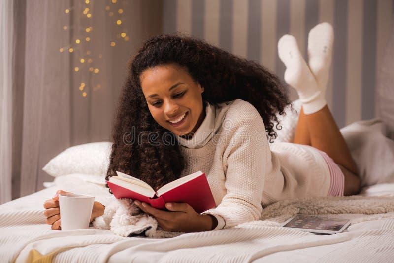 Vrouw die met mok en boek leggen stock afbeeldingen