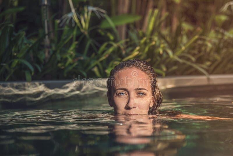 Vrouw die met mooie blauwe ogen uit de pool met neus onder water kijken stock foto's