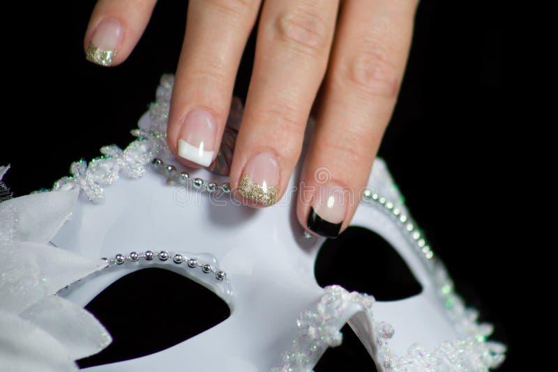 Vrouw die met mooie spijkers een wit Carnaval-masker houden royalty-vrije stock afbeelding
