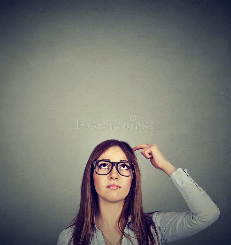 Vrouw die met nadenkende uitdrukking omhoog op grijze muurachtergrond kijken royalty-vrije stock afbeelding