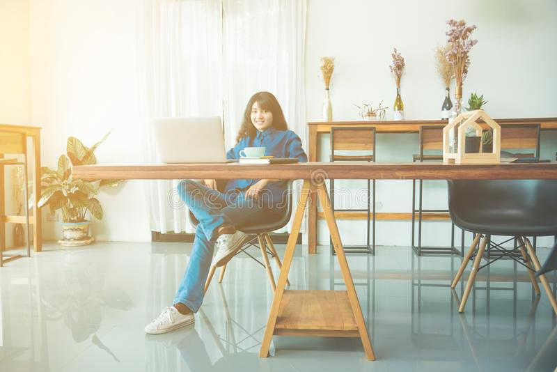 Vrouw die met notitieboekjecomputer werken terwijl het drinken van koffie stock afbeelding