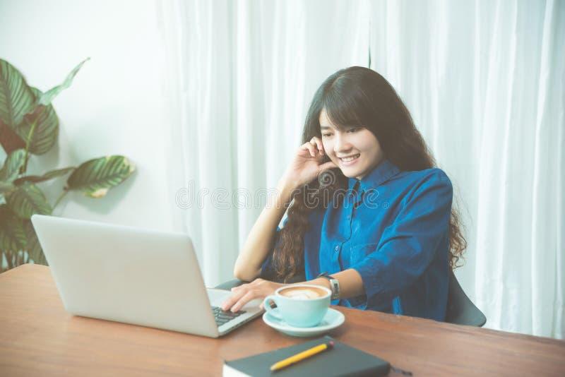 Vrouw die met notitieboekjecomputer werken terwijl het drinken van koffie stock foto