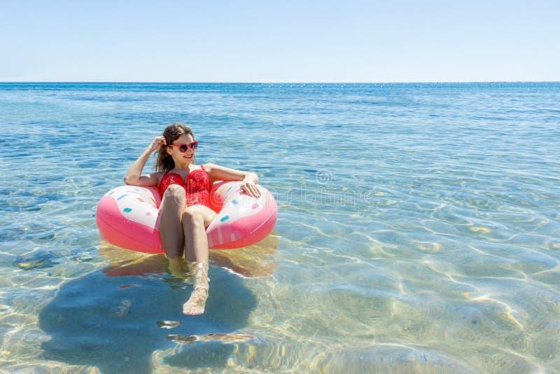 Vrouw die met opblaasbare doughnut op het strand in de zomer zonnige dag zwemmen stock afbeelding