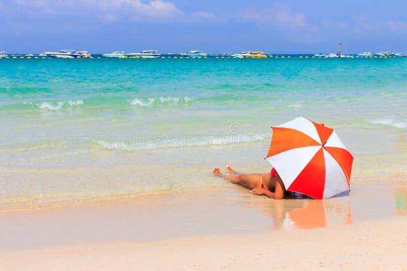 Vrouw die met oranje paraplu's zonnebaden stock foto