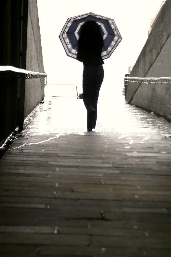 Vrouw die met Paraplu loopt stock afbeeldingen