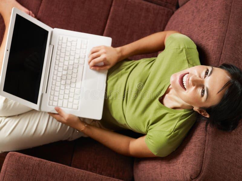 Vrouw die met PC op bank lacht stock foto