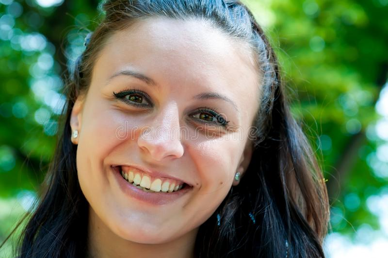 Vrouw die met perfecte glimlach en witte tanden in een park glimlachen stock foto's