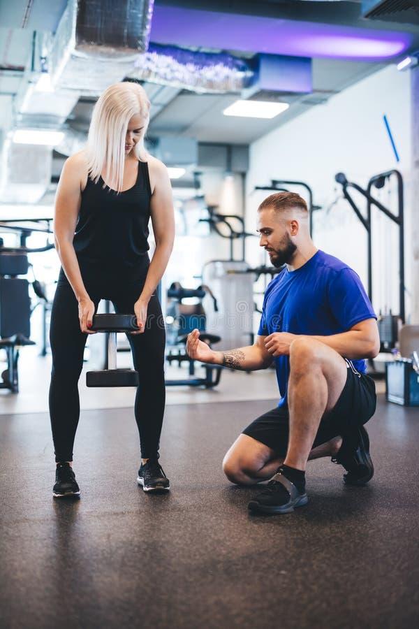 Vrouw die met persoonlijke trainer uitoefent stock afbeelding