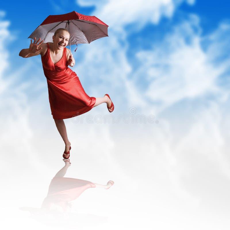 vrouw die met rode paraplu in wolken danst stock fotografie