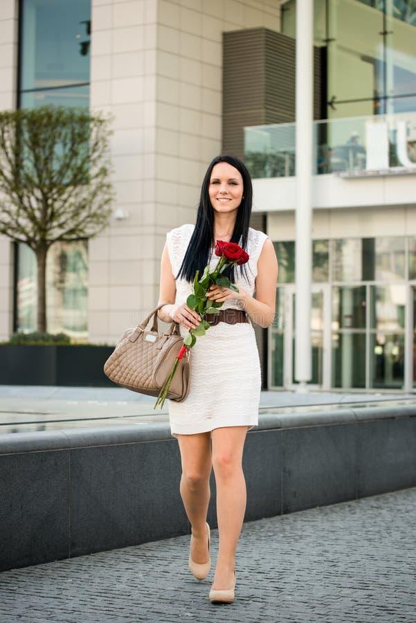 Vrouw die met rozen straat lopen royalty-vrije stock foto's