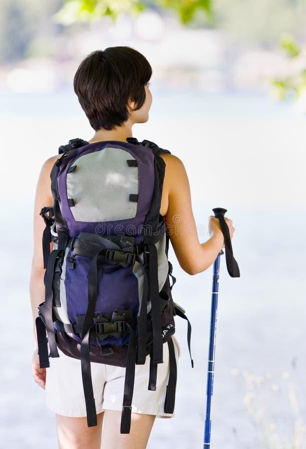 Vrouw die met rugzak en wandelstok wandelt stock afbeeldingen