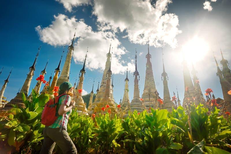 Vrouw die met rugzak reizen die stupa Boeddhistische tempel bekijken stock foto