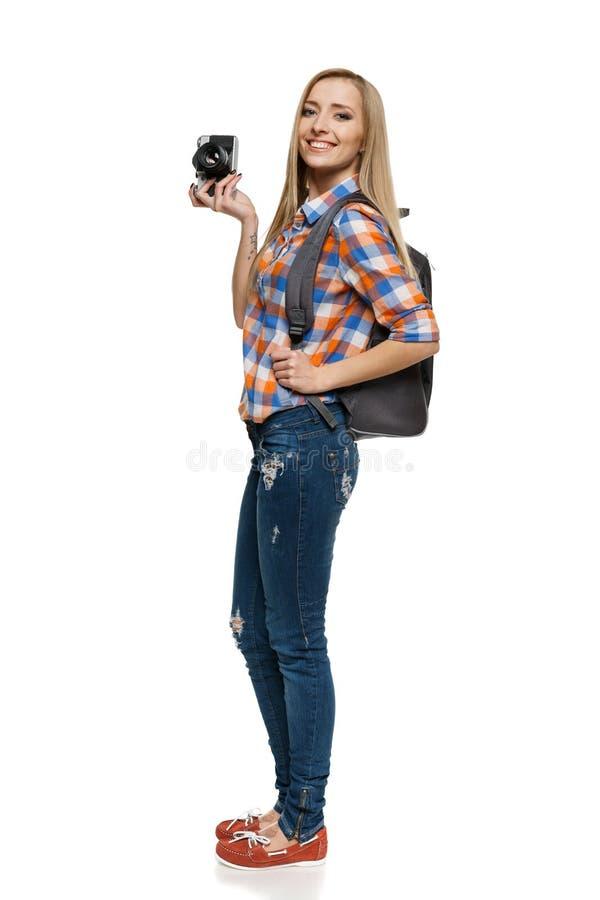 Vrouw die met rugzak retro camera houden royalty-vrije stock afbeelding