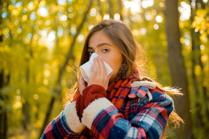 Vrouw die met servet in het gele park niezen De zieken heeft lopende neus Allergieseizoen De vrouw maakt een behandeling voor stock afbeeldingen