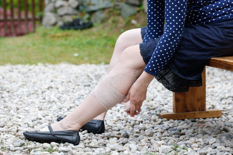 Vrouw die met spataders compressieverband toepassen stock foto's