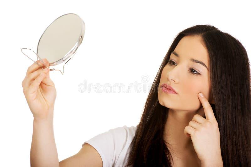 Vrouw die met spiegel pukkels controleren royalty-vrije stock fotografie