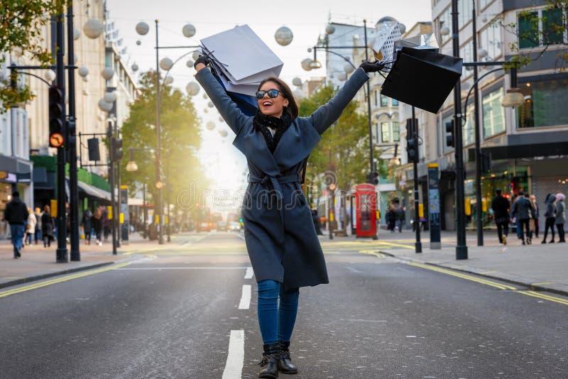 Vrouw die met vele het winkelen zakken in haar hand onderaan Oxford Street lopen stock afbeeldingen