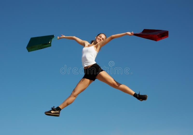 Vrouw die met zakken springt stock fotografie