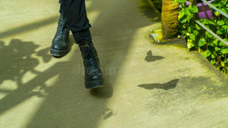 Vrouw die met zwarte laars op tropische vlindertuin en schaduw van vlinder op grond lopen royalty-vrije stock afbeelding