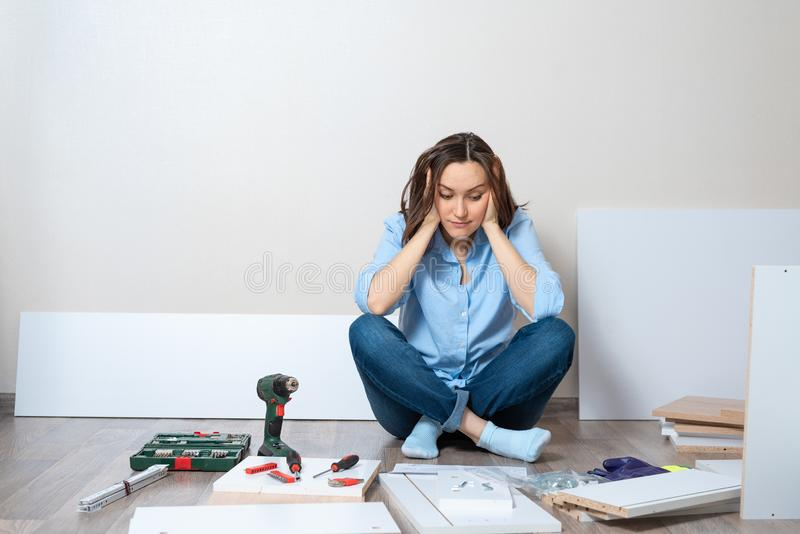 Vrouw die meubilair proberen te assembleren en te installeren stock afbeeldingen