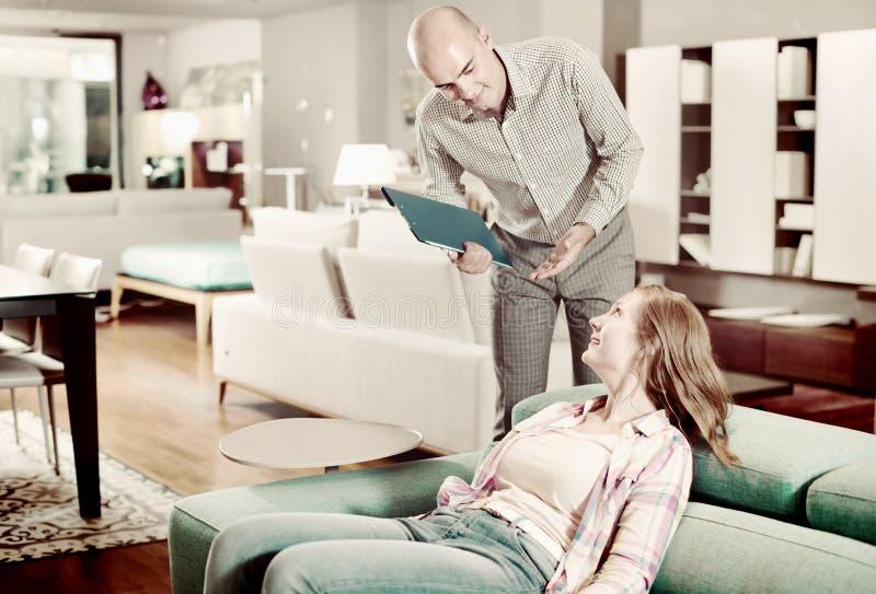 Vrouw die meubilair voor flat kiezen stock afbeeldingen