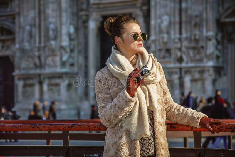 Vrouw die in Milaan afstand onderzoeken terwijl het houden van fotocamera stock foto's