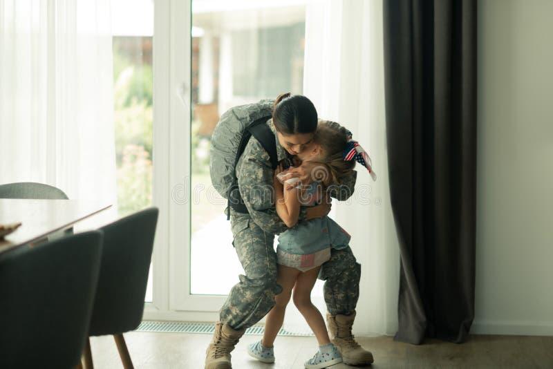 Vrouw die militaire eenvormig dragen koesterend haar dochter stock fotografie