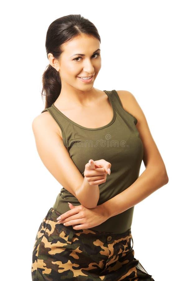 Vrouw die in militaire kleren op u richten stock fotografie