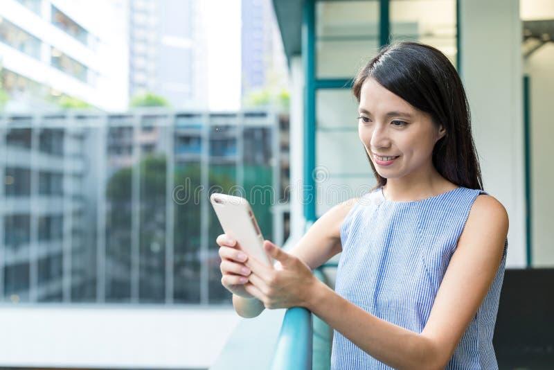 Vrouw die mobiel buitenbureau gebruiken stock afbeeldingen