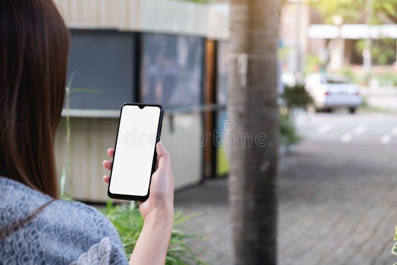 Vrouw die mobiele telefoon, buitenshuis, mock-up op scherm gebruikt royalty-vrije stock afbeelding