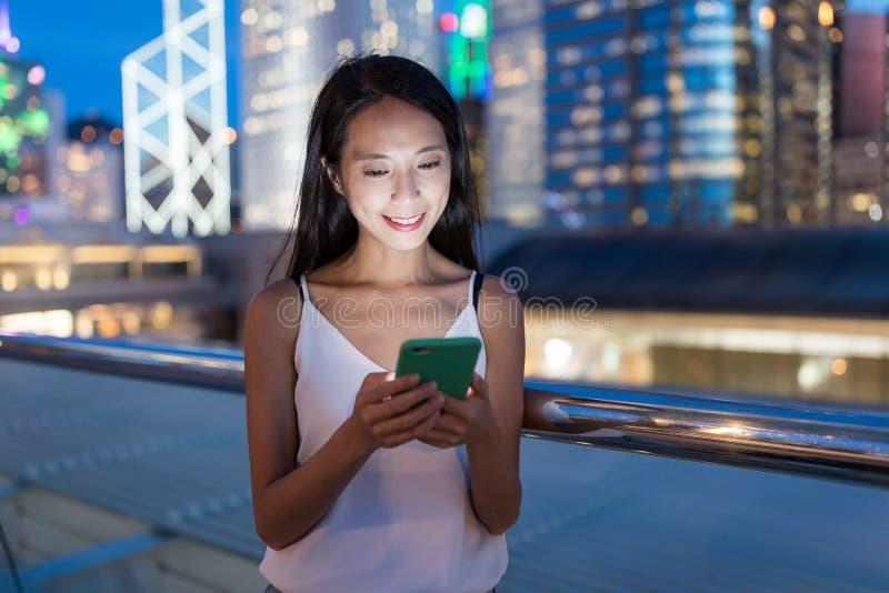 Vrouw die mobiele telefoon in de stad met behulp van bij nacht royalty-vrije stock afbeeldingen