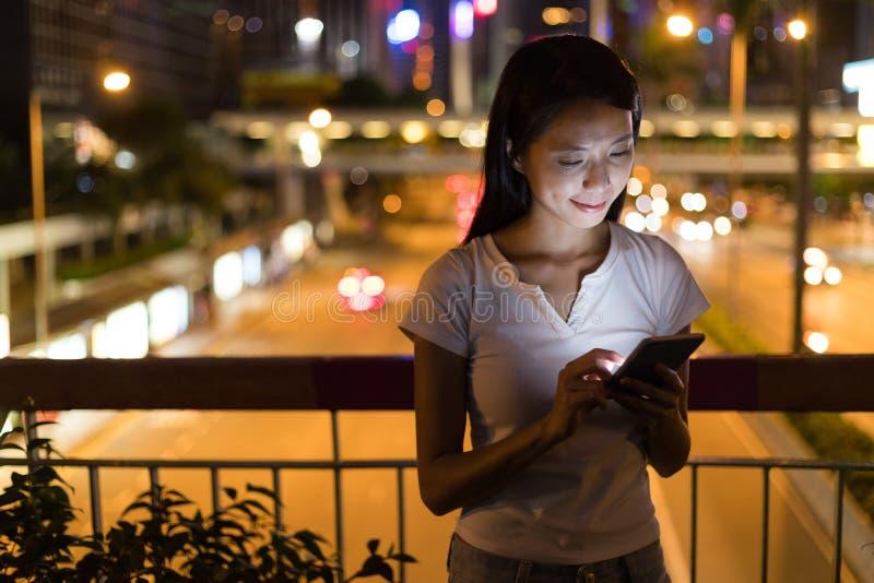 Vrouw die mobiele telefoon in de stad van Hong Kong met behulp van bij nacht royalty-vrije stock fotografie