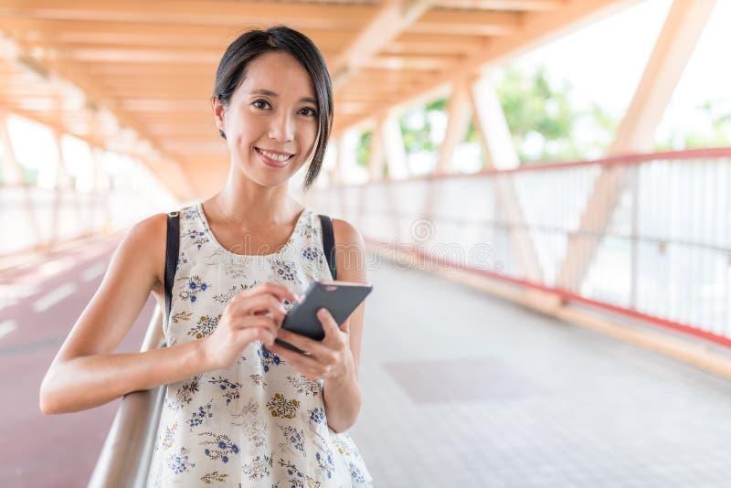 Vrouw die mobiele telefoon in de straat met behulp van stock afbeelding
