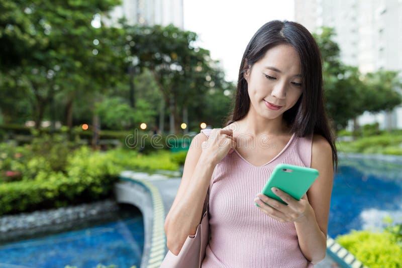 Vrouw die mobiele telefoon in het park bekijken royalty-vrije stock fotografie