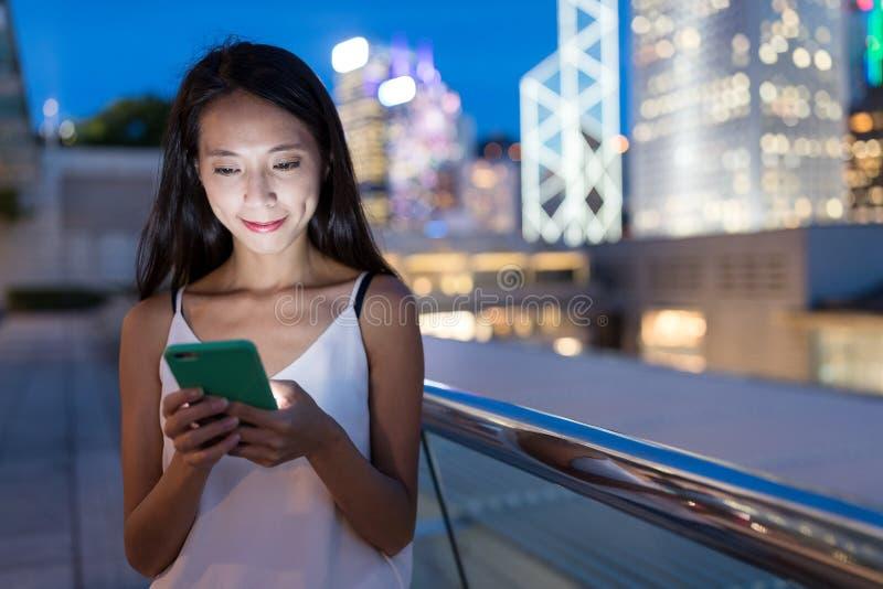 Vrouw die mobiele telefoon in Hong Kong-stad met behulp van stock fotografie