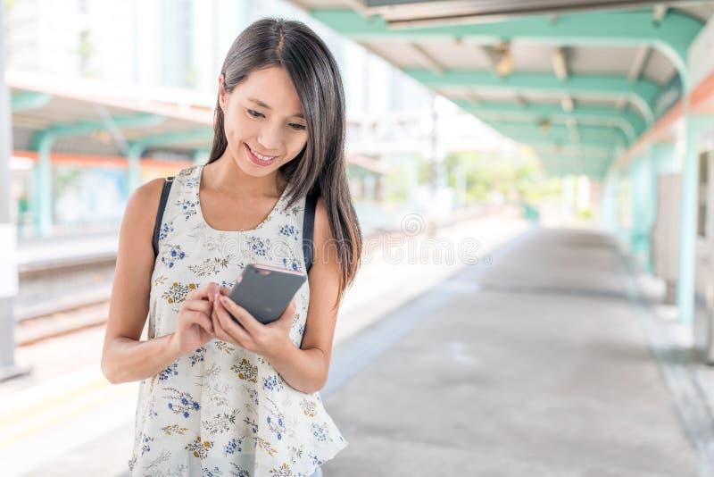 Vrouw die mobiele telefoon in lichte spoorpost met behulp van stock afbeelding