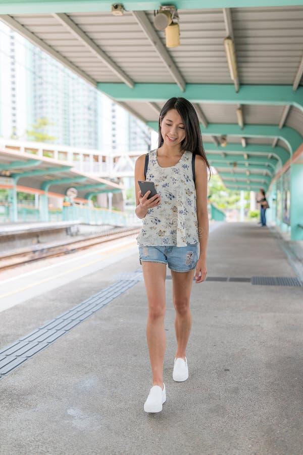 Vrouw die mobiele telefoon in lichte spoorpost met behulp van van Hong Kong royalty-vrije stock afbeelding