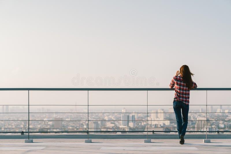 Vrouw die mobiele telefoon met behulp van bij dak tijdens zonsondergang met exemplaarruimte, mededeling of eenzaam mensenconcept royalty-vrije stock foto
