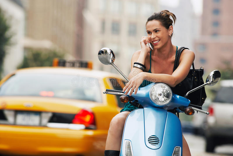 Vrouw die Mobiele Telefoon op Bromfiets met behulp van stock afbeeldingen