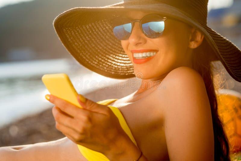 Vrouw die mobiele telefoon op het strand met behulp van stock afbeelding