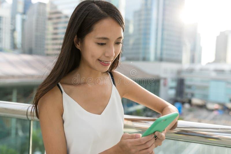 Vrouw die mobiele telefoon in stad bekijken stock afbeeldingen