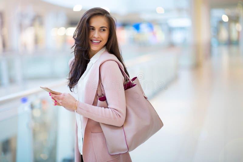 Vrouw die mobiele telefoon in winkelcomplex met behulp van royalty-vrije stock foto