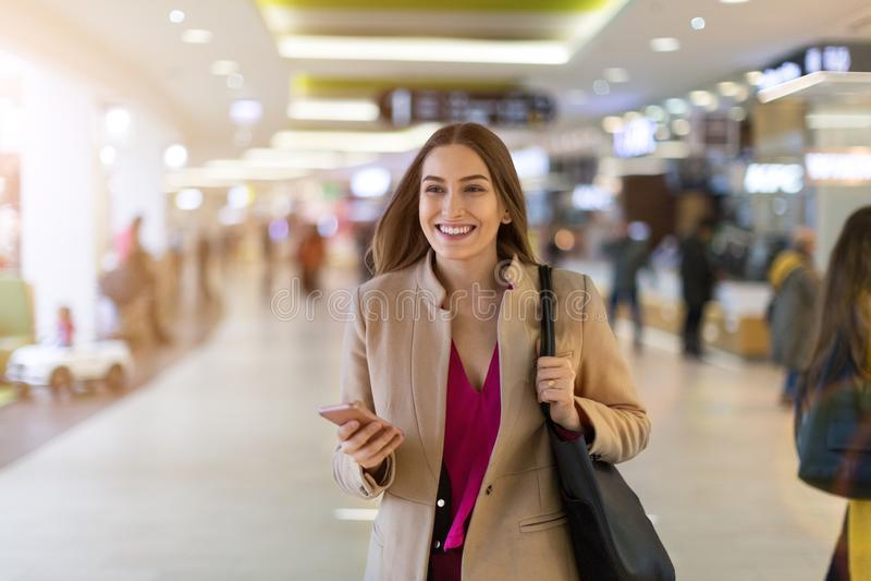Vrouw die mobiele telefoon in winkelcomplex met behulp van royalty-vrije stock fotografie